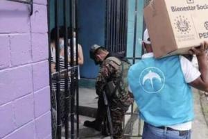 Two people stand in a doorway as one person wearing a military uniform approaches followed by another person with a teal vest with GANA (previously Nuevas Ideas logo) carrying a box marked with Salvadoran government logo.